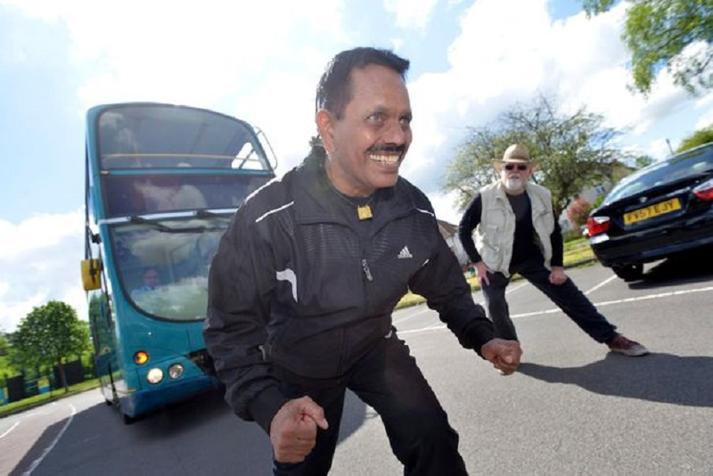 عجوز هندي يجر باص بشعره