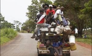 اشخاص كثر يجلسون فوق سيارة وداخل الصندوق